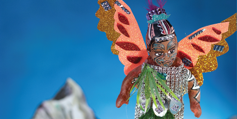 A handmade model figure with orange and gold wings, and a mountain in the distance.