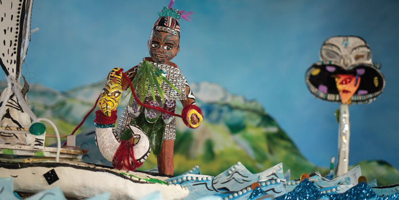 A handmade model figure standing on a canoe at sea, holding a large fish hook on a rope.