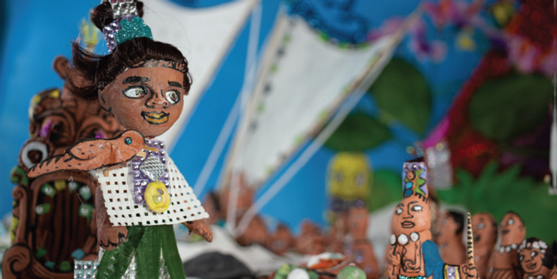 A model figure standing up with a bird on his shoulder and the sails of a canoe behind him. To the right are several other figures.