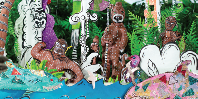 Models of brown grimacing creatures coming out of the forest, with pink and blue sharks in the sea in front.