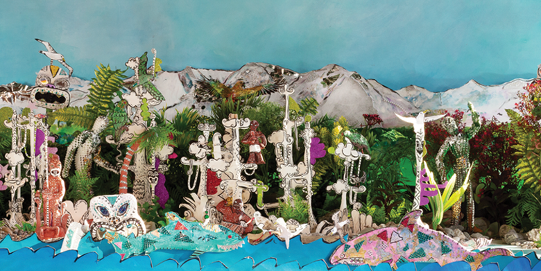 Handmade model sharks in the sea in front of model forests and snowy mountains, with flying birds and other creatures.